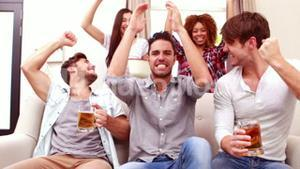 Friends watching sport on tv and drinking beer