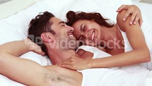 Happy couple laughing in bed