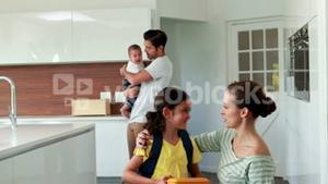 Child ready to school in the kitchen with family