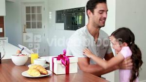 Cute girl giving present to father