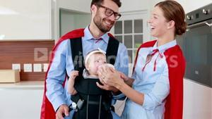 Parents with red cloak feeding their baby