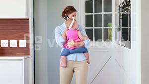 Businesswoman in a phone call while rocking her baby