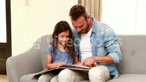 Happy father and daughter reading a book