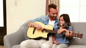 Happy father and daughter playing guitar