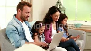 Happy family using devices on sofa