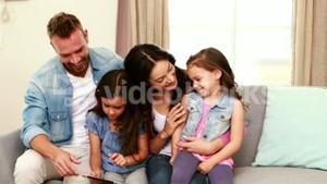 Happy family using tablet on the sofa