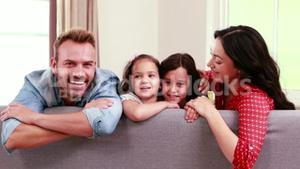 Smiling family posing on sofa