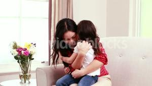 Mother and daughter hugging on sofa