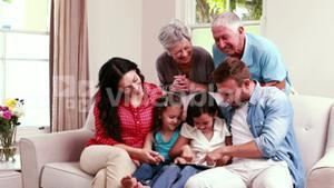 Smiling family using tablet on sofa