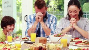 Family praying before eating lunch