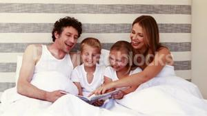 Happy family reading book on the bed