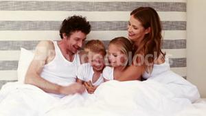 Happy family playing on bed