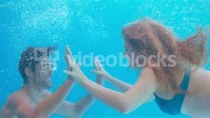Happy couple swimming underwater