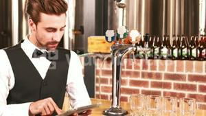 Smiling barkeeper using tablet well dressed
