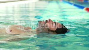 Muscular man floating with closed eyes