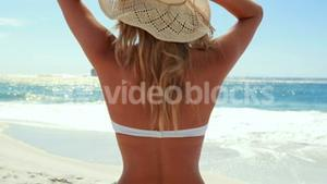 Attractive blonde with hat at the beach