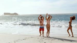 Happy friends jumping at the beach