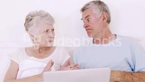Senior couple in bed talking