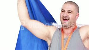 Happy athlete with medal holding flag