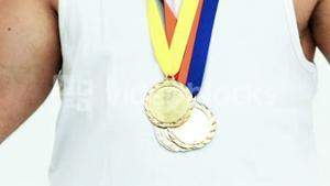 Mid section of happy athlete with medals
