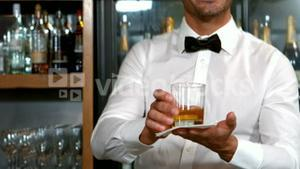 Smiling barman serving a whisky