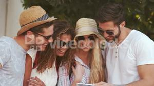 Smiling hipster friends looking at smartphone