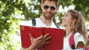 Smiling hipster couple reading book