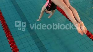 Fit woman swimmer diving into pool
