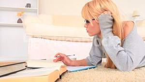 Young blondhaired woman studying