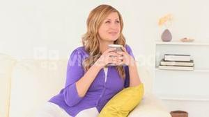 Attractive blondhaired woman thinking while drinking cofee