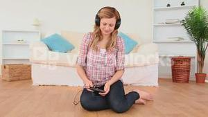 Happy blondhaired woman listening to music at home