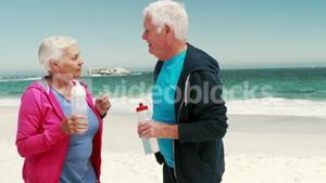 Old retired couple drinking water after sport
