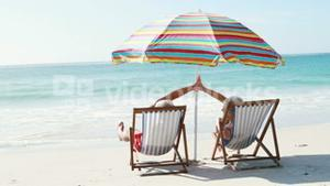 Retired old couple lying on deckchair while doing high five