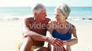 Retired old couple sitting on towel