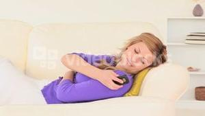 Blondhaired woman taking a nap then answering the phone