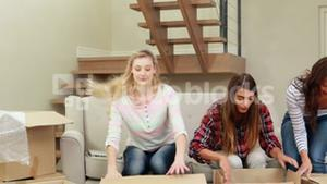 Smiling women opening boxes