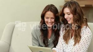 Happy brunettes using tablet