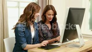 Creative businesswomen using computer and digital board