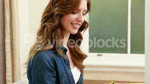 Smiling brunette using computer and digital board
