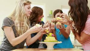 Happy friends eating cake with hands