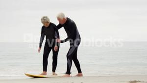 Mature man explaining to woman how to surf