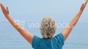 Woman facing the sun with open arms