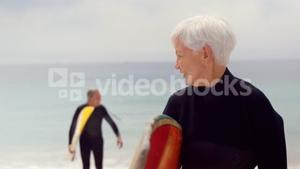 Retired couple holding surfboards