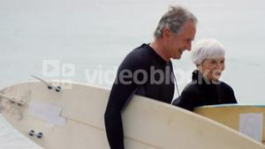 Retired couple walking with surfboards
