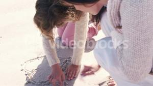 Mother and daughter drawing in the sand