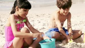 Cute siblings building a sand castle