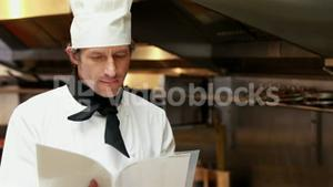 Handsome chef reading recipes