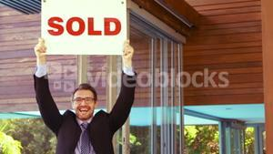 Estate agent cheering and holding SOLD sign