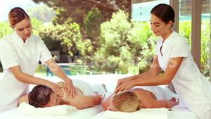 Cheerful masseurs messaging relaxed couple