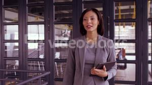 Businesswoman walking with tablet